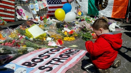 Two-year-old Wesley Brillant of Natick, Massachusetts kneels in front of a memorial to the victims of the Boston Marathon bombings near the scene of the blasts on Boylston Street in Boston